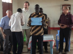 A proud priest holds his graduation certificate from the Alpha/PRMI training held in Aweil, South Sudan from January 31 - February 6, 2013.